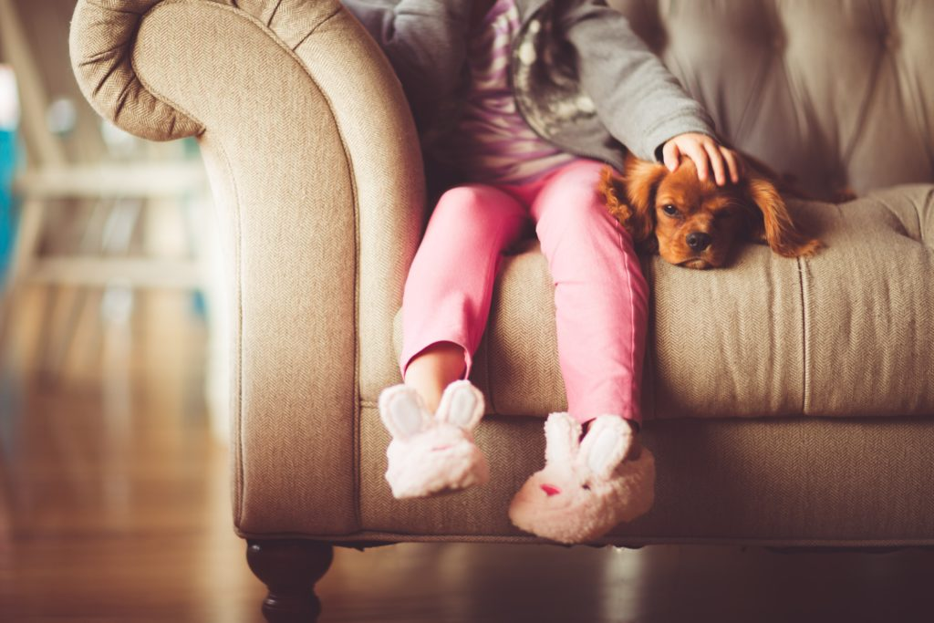 Small girl with pink pants wearing bunny slippers sitting on couch with her hand on the head of a puppy | New Coastal