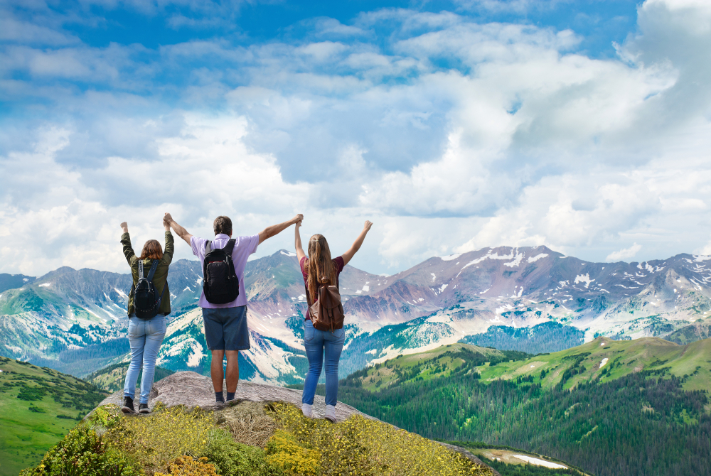 Three day hikers enjoying view of valley from the top of a rock | New Coastal