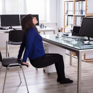 Woman in blue sweater exercising at her desk using her work chair for support | New Coastal
