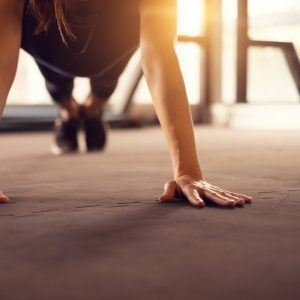 Partial front view of woman doing push-ups on a gray floor | New Coastal