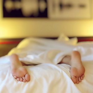 Feet of woman sleeping on her stomach sticking out from under bedding | New Coastal