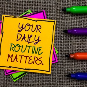 "Stack of yellow, fuschia & green notes with inscription ""Your Daily Routine Matters"" and 4 green, purple, red and blue markers 